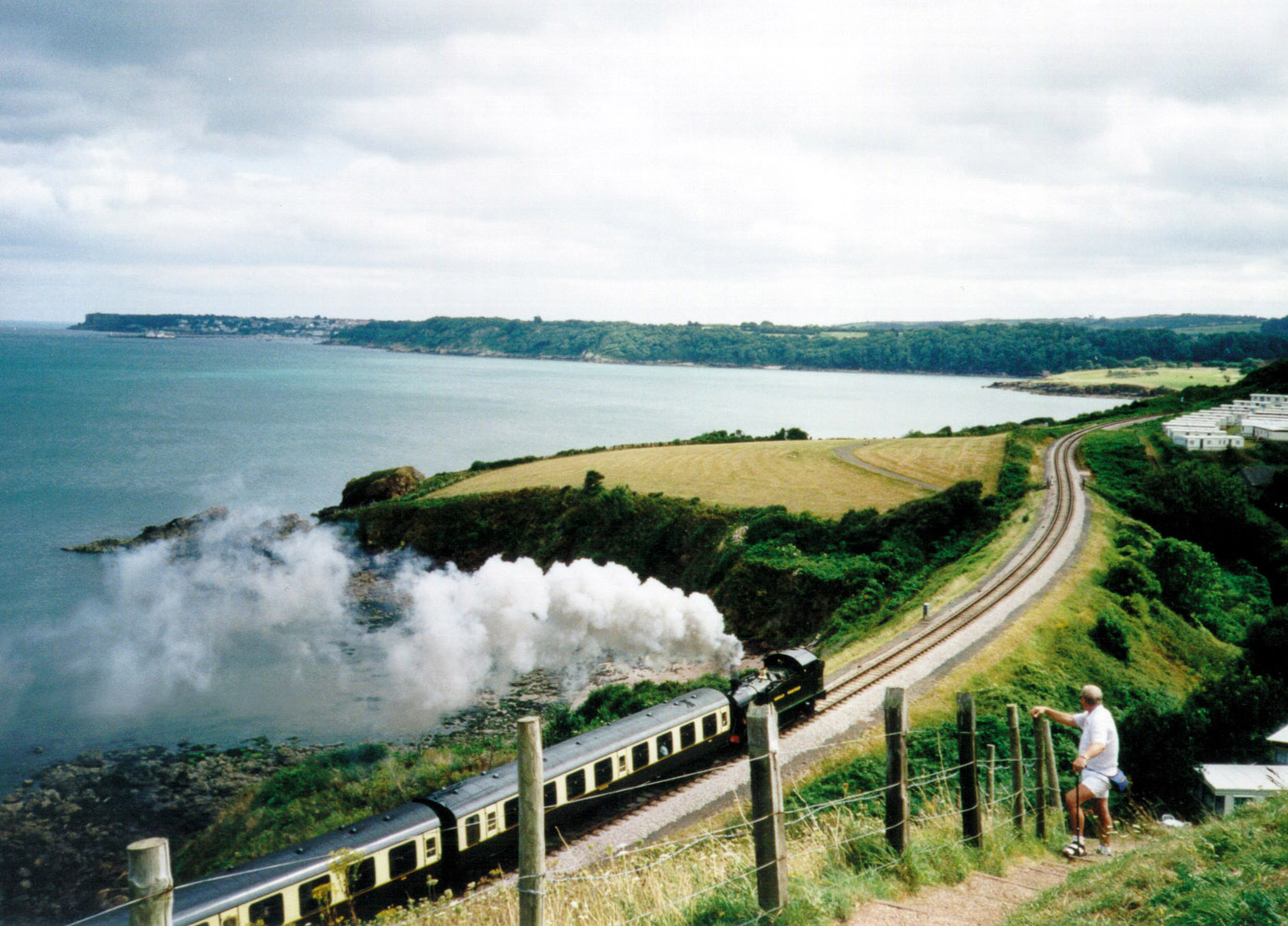 A romantic view of a steam train passing along the coast between Paignton and Dartmouth