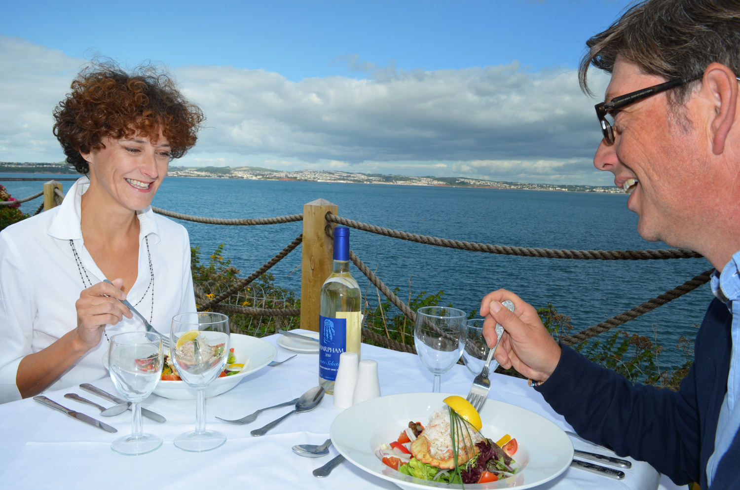 A couple having a romantic lunch with a view over the Devon coastline near Torquay.