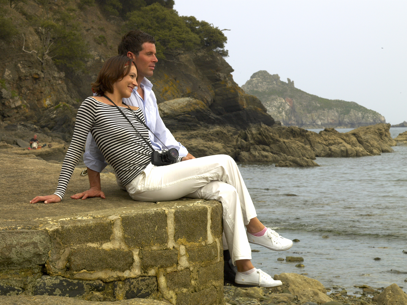 A young couple enjoying a romantic break on the beach in Torquay, Devon